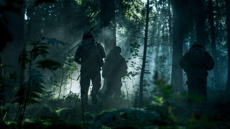 Sotilaita silhuetteina hiipimässä metsässä.