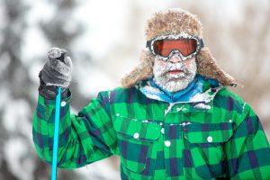 Mies talvivaatteissa lunta parrassa.